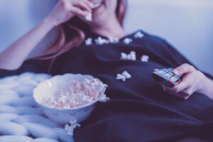 uśmiechnięta dziewczyna je popcorn przed telewizorem
